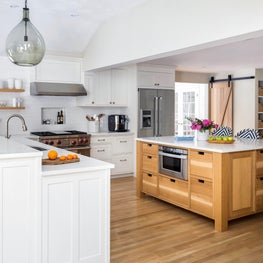 Open plan custom warm white kitchen w/ oak island w/ cutout pulls, barn door