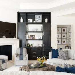 Traditional living space with lots of seating for a large family and floor to ceiling dark stained built ins with shelving and cabinets