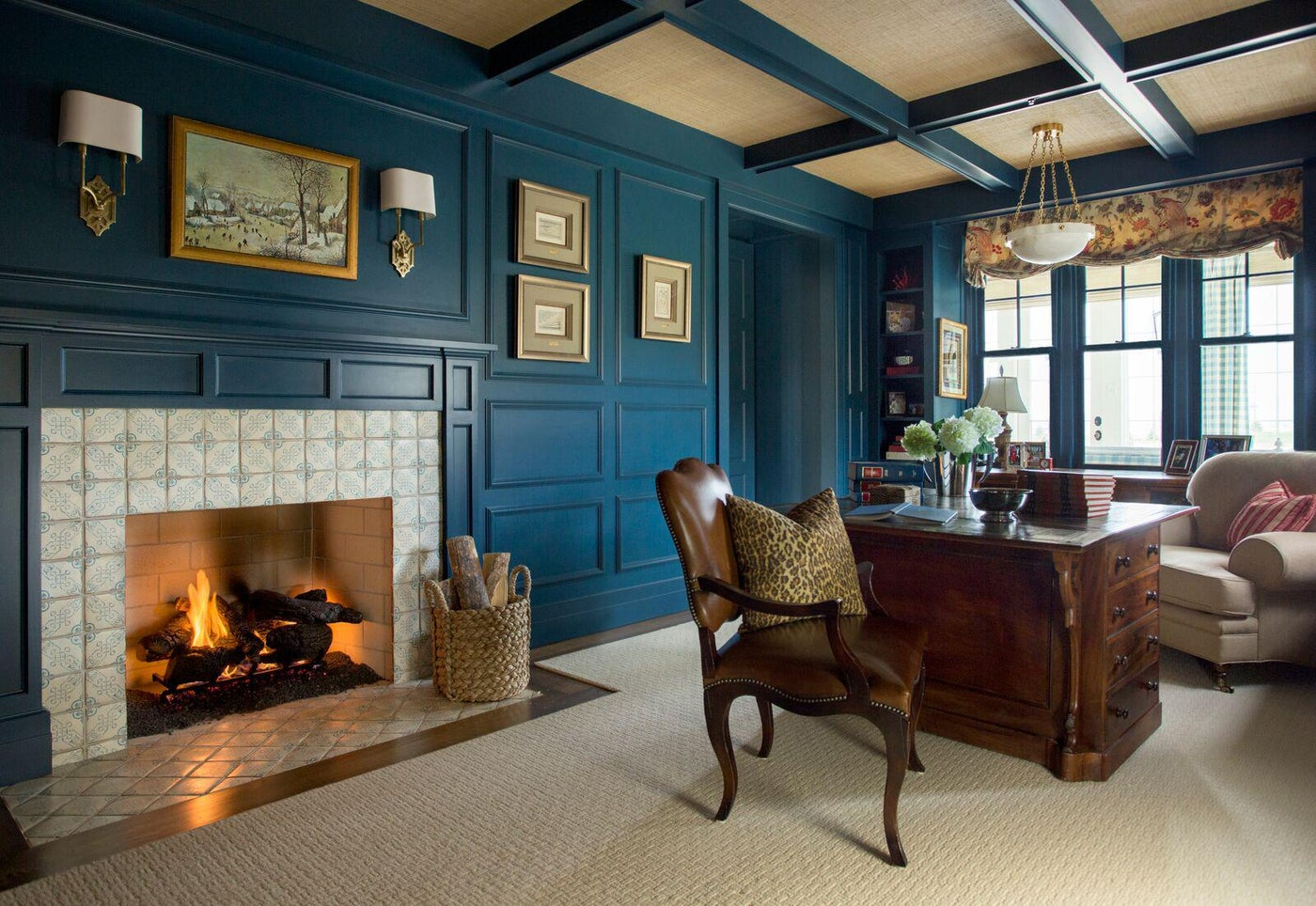 Library with blue-paneled walls, tile fireplace, coffered ceiling