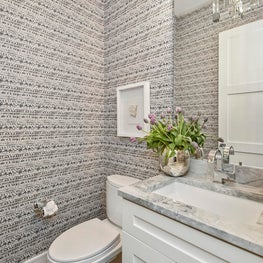 Geometric patterned wallpaper adds a whimsical flair to this powder room.