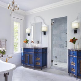 Twin vanities set on profiled marble wall frames which flank a marble shower