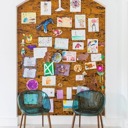 Large cork pin board display for kids' artwork in contemporary style home