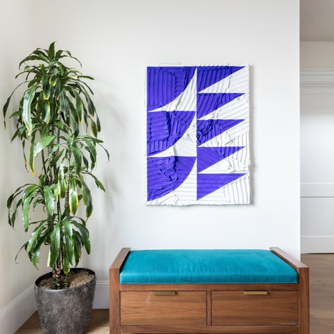 Bold color and geometric shapes overlay a textural ground in this abstract painting. A custom storage bench upholstered in a deep teal linen textile creates a convenient spot for removing shoes just inside the front door.