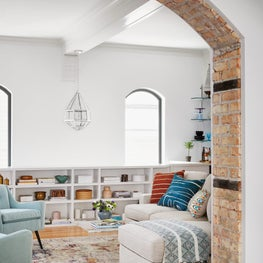 Historic Bucktown Condo Living Room with Exposed Brick Arch and Built-in Bookshelves