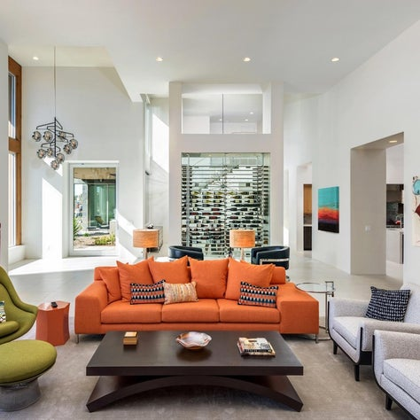 Glass walled wine storage adds a stunning backdrop to a modern airy living room