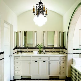Spanish style master bath with barrel-vault ceiling, double vanity, and bath