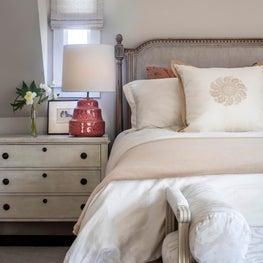 Bedroom w/ red lamps, divan, Swedish chest bedside tables, grey linen velvet bed