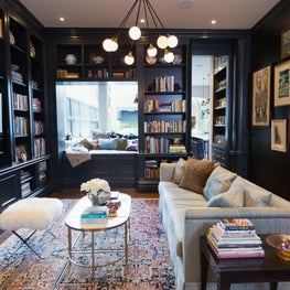 Eclectic library with high gloss cabinetry and built in window seat