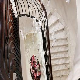 A grand black wrought-iron staircase with a bespoke Swarovski cascading chandelier.