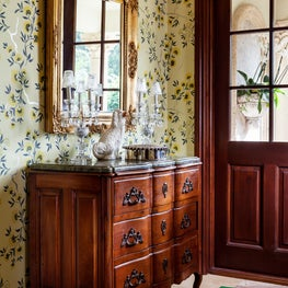 Colorful wallpaper & an antique walnut marble top chest is in the foyer.