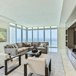 Modern, neutral living room with water views and pop of color.
