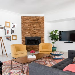 Colorful media room featuring wood accented fireplace and yellow accents