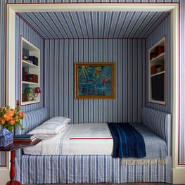 Built-in bed with shelving and blue striped wallpaper