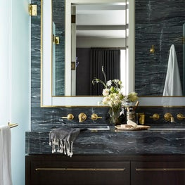 Modern master bathroom with custom marble and brass plumbing fixtures