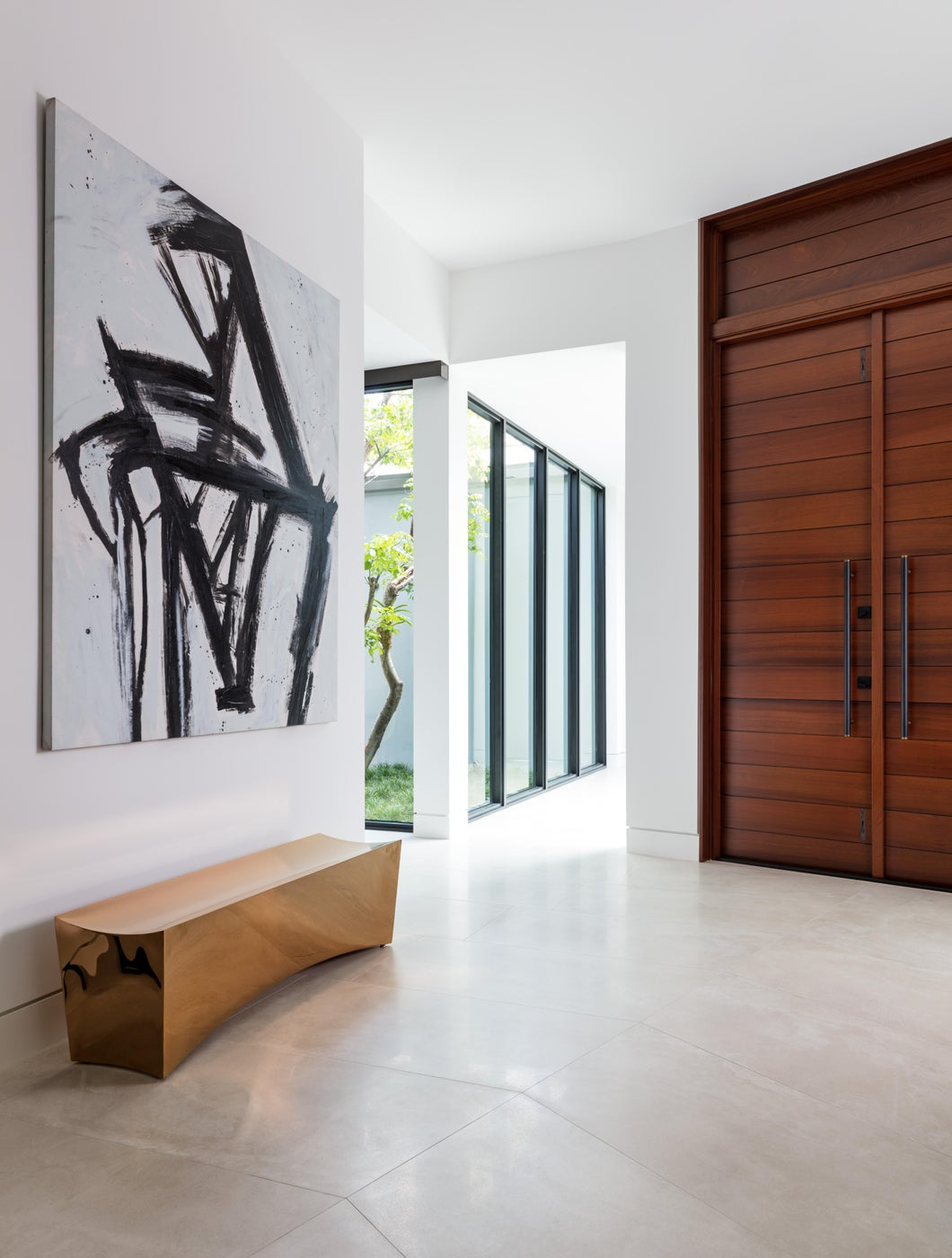 Entryway with dramatic art and custom contemporary bench