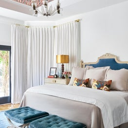 Master Bedroom with Upholstered Headboard, Benches, and a Wallpapered Ceiling