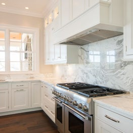 Kitchen with White Cabinets and Full height Marble Slab Backsplash