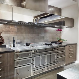 Moody Modern bachelor kitchen. Black counter tops with polished custom hood.