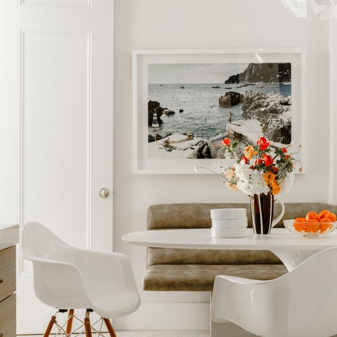 Madison Avenue Kitchen with Upholstered Banquette, Eames Fiberglass Shell Armchairs and Alden Baker Ceramics