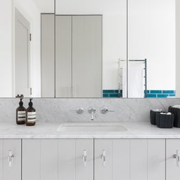 Tongue and groove detail in family bathroom with carrera marble tops