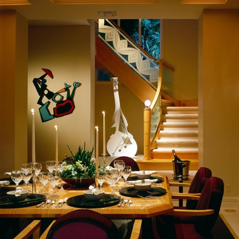 Custom wood and glass stairway is the backdrop for this contemporary dining area