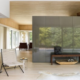 A gray lacquer wall creates a separation between this home's entry and kitchen.