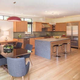 Open kitchen with streamlined, minimal, detailing. Open to patio and living area