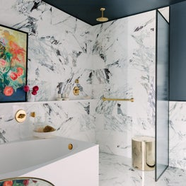 Marble Bathroom with abstract art, reeded glass panel, and brass fixtures