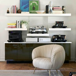 Custom plaster shelves house the homeowners' record player and music equipment.