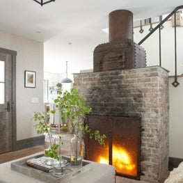 Montana luxury farmhouse with fireplace from vintage brick with kitchen beyond