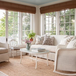 Sunroom in a coastal home is decorated with new and vintage wicker furniture