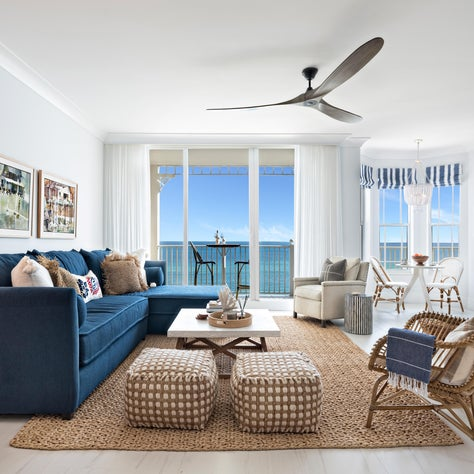 Coastal living room with blue sofa and rattan chairs. The porcelain floors add a nice modern touch.