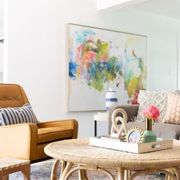 Light-filled living room with cane rattan table, abstract art, & coastal accents
