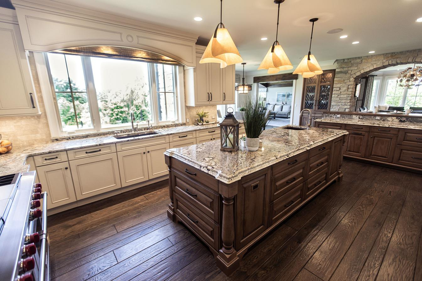 Two islands in white and wood stained kitchen, wood floor, granite counters