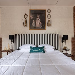 Rustic bedroom with brick fireplace details and striped upholstered headboard