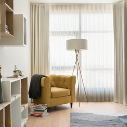 Modern guest bedroom with yellow chair, floor lamp, and white curtains