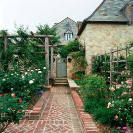 Rose garden with a view of the Country French stonehouse.