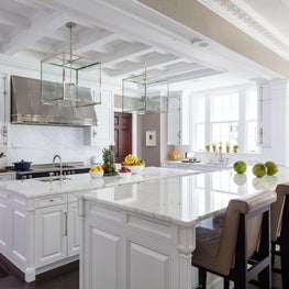 This white kitchen has coffered ceiling, custom millwork & double islands.