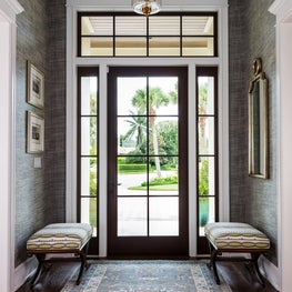 Upon entry there is a blue patterned area rug by Lee Jofa.