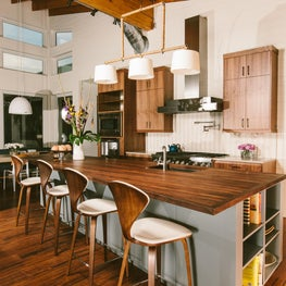 Walnut  countertops, bamboo wood floors , and exposed ceiling in  family kitchen