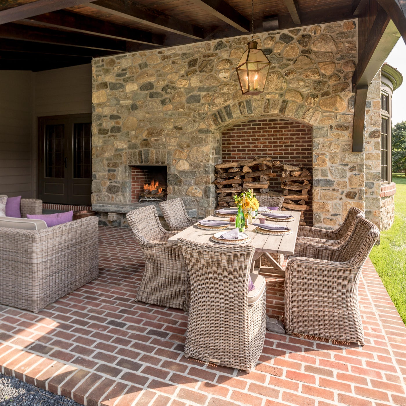 Traditional Covered brick Terrace with stone fireplace and custom wood storage