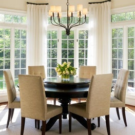 Round dining table and chairs in light filled dining room w/ custom drapes, rods