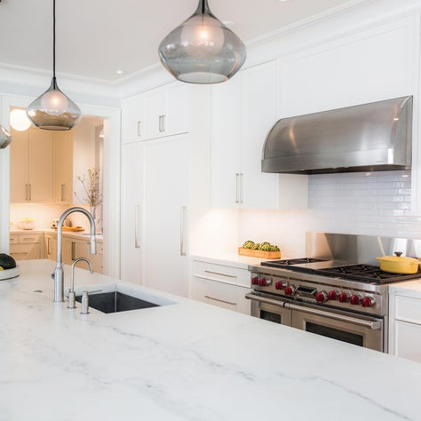 White Kitchen with Calacatta Michelangelo counters and Smoke Glass Pendants