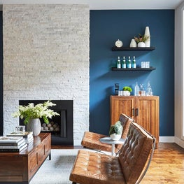Contemporary Living Room with Vintage Barcelona Chairs, Dark Blue & Wood Accents