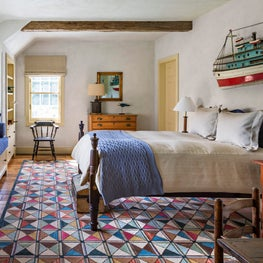 A vibrant hooked rug is a playful touch in this young boy's bedroom.