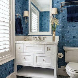 This white powder room showcases bold blue patterned wallpaper and vibrant floor tiles.