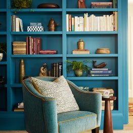 Custom built bookshelf with antique reupholstered armchair