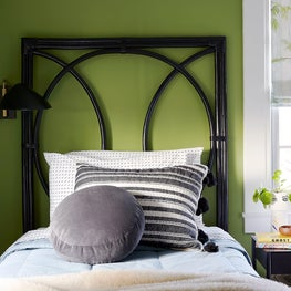 Girls bedroom with geometric headboard and green wall color