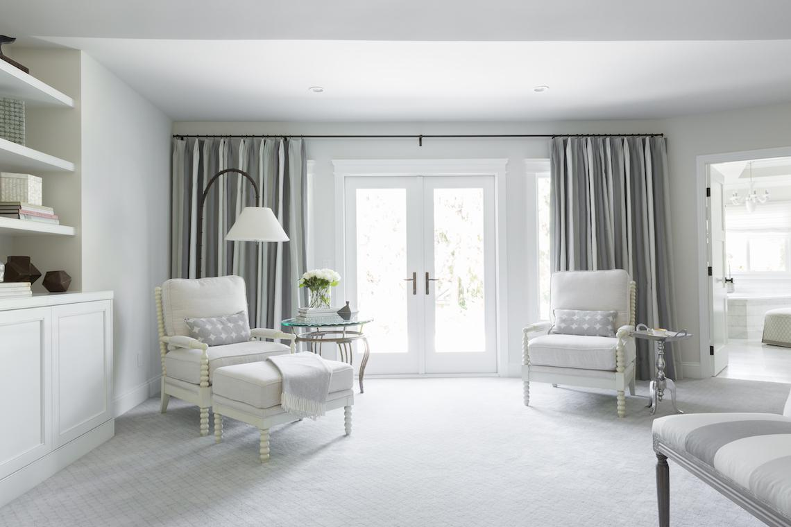 Master bedroom seating area with custom black out window treatments.