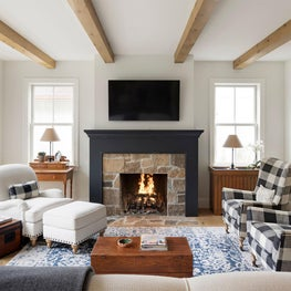 A historic stone and wood-framed fireplace in this living room